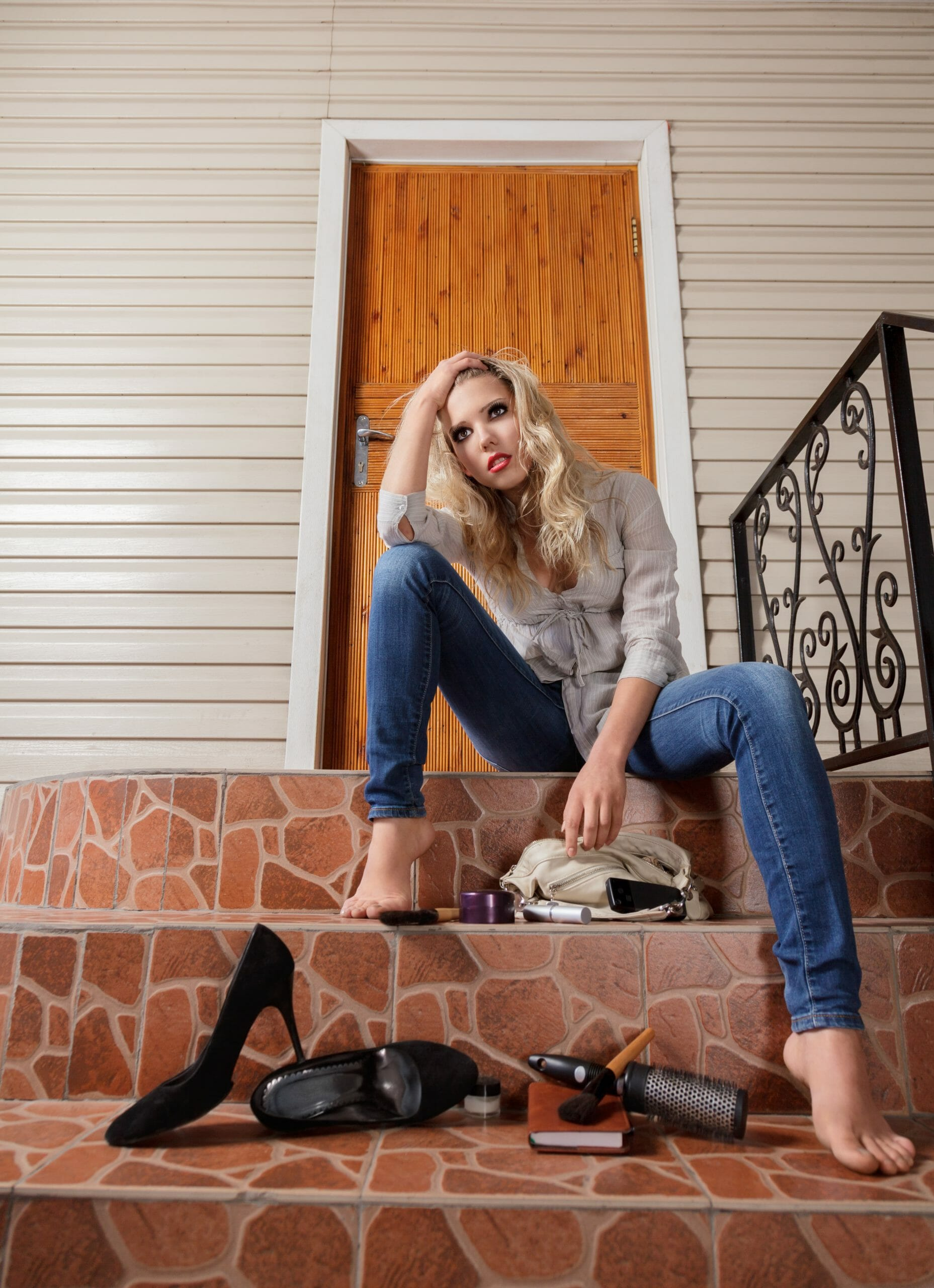Young sad woman lost her house keys. Girl sits in front of the door